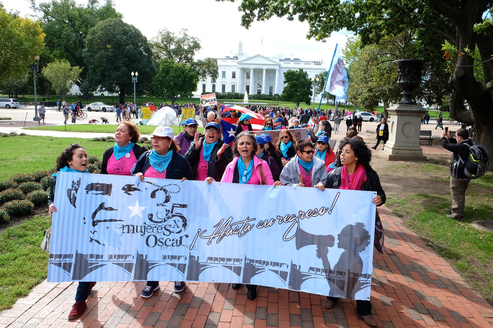 Women marching with a banner for the freedom of Oscar Lopez