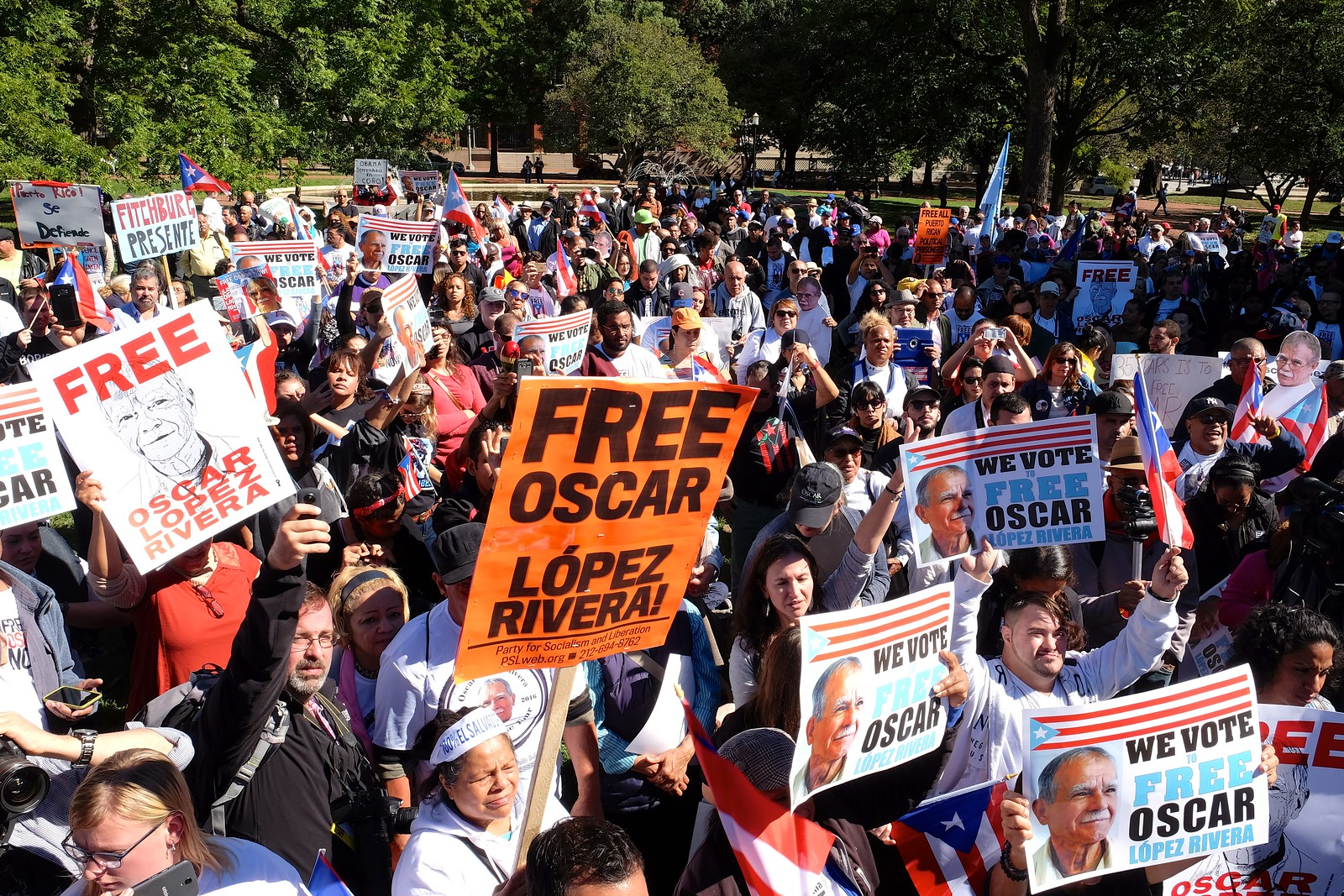 A large crowd gathers to show support for the freedom of Oscar Lopez, holding placards and Puerto Rican flags.
